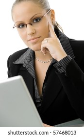 Young businesswoman sitting at desk working on laptop computer, isolated on white background.
