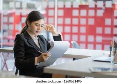 young businesswoman sitting at her desk in an office reading report on paper