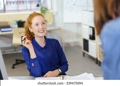 Young businesswoman sitting at her desk looking up and listening to a female colleague with a smile and attentive expression