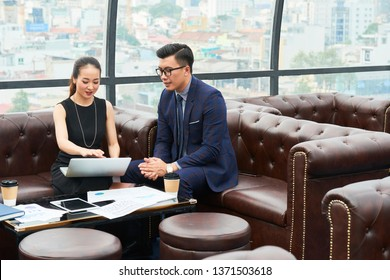 Young businesswoman sitting with laptop and explaining her online presentation to her colleague during a business meeting