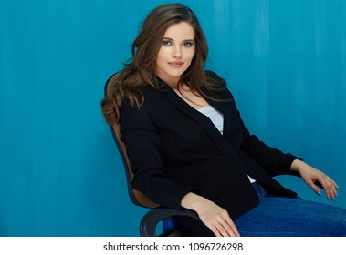 Young businesswoman sitting in office chair. Blue wall background.