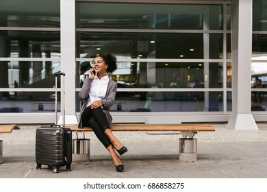 Young businesswoman sitting on a bench and talking on smartphone at airport terminal