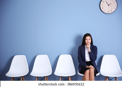 Young businesswoman sitting on a chair in blue hall