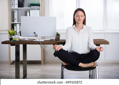 Young Businesswoman Sitting On Chair Doing Meditation