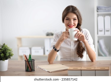 Young businesswoman sitting on the desk with  with cup