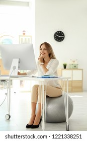 Young businesswoman sitting on fitness ball and using computer in office. Workplace exercises