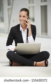 Young businesswoman sitting on floor using laptop and cellphone