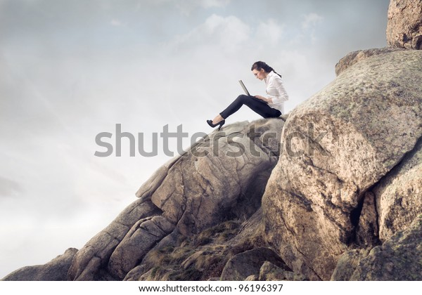 Young businesswoman sitting on a peak in the mountains and using a laptop