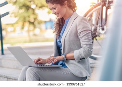 Young businesswoman sitting on stairs and using laptop outdoors.