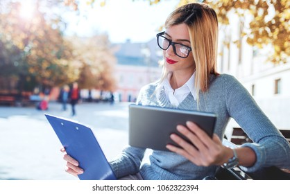 Young businesswoman sitting in the park and working with digital tablet, checking a notes. Business, education, lifestyle concept