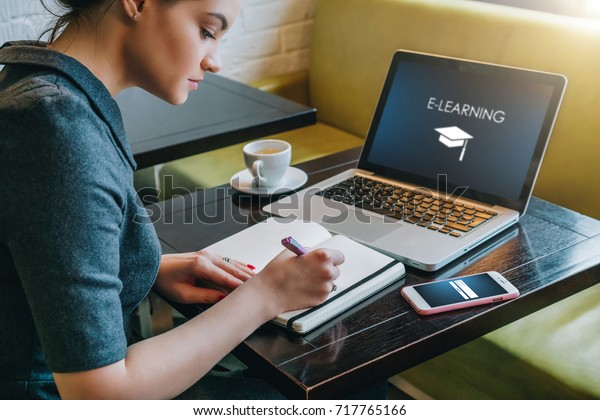 Young businesswoman sitting at table in cafe in front of laptop with inscription on screen e-learning and image of square academic cap and making notes in notebook,diary. Online education,e-learning.