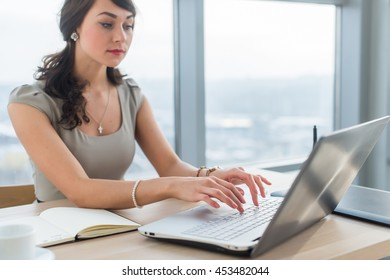 Young businesswoman sitting at work desk, reading and typing new e-mail, using internet on the portable computer