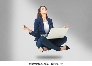 Young businesswoman sitting in yoga lotus position with laptop. Beautiful business woman meditating and making yoga