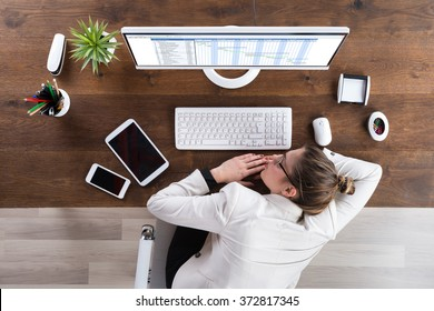 Young Businesswoman Sleeping In Front Of Computer At Desk