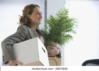 A young businesswoman smiles as she carries her office belongings in her hands.  Horizontal shot.