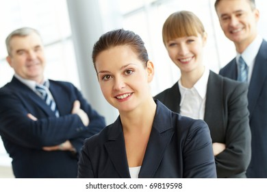 A young businesswoman smiling against her three colleagues