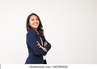 Junge Geschäftsfrau lächelt die Kamera an. Porträt einer schönen, glücklichen jungen Frau, die mit gekreuzten Armen steht und die Kamera einzeln auf grauem Hintergrund betrachtet. Emotion-Konzept