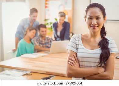 Young businesswoman smiling at the camera while her team is discussing