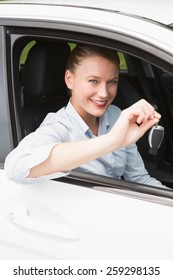 Young businesswoman smiling and holding key in her car