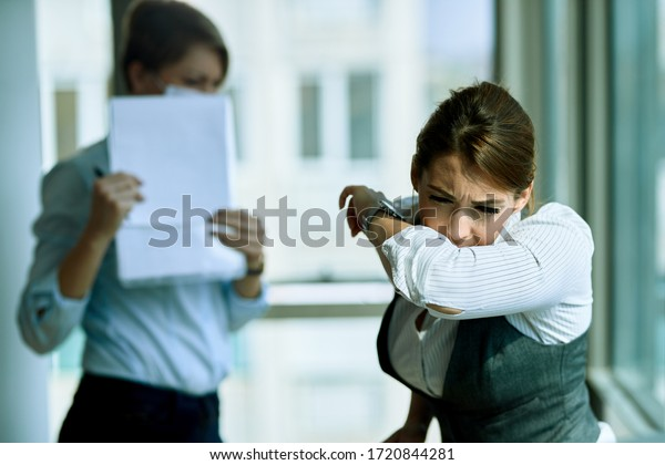 Young businesswoman sneezing into elbow while being in the office. Her colleague is in the background.