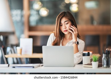 young businesswoman speaking on the phone with her customer in comfortable workplace