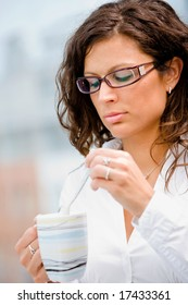 Young businesswoman standing in front of office window, drinking coffee and thinking.