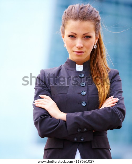 young businesswoman standing in front of office buildings