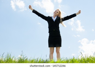 Young Businesswoman Standing In Grass With Arm Extended