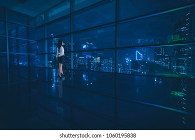 Young businesswoman standing in the office while looking at a beautiful city at night