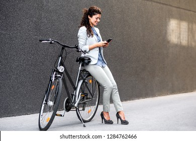Young businesswoman standing on a city street with bicycle looking at phone.