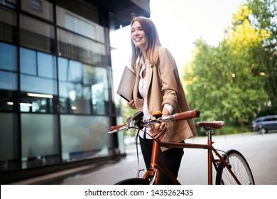 Jeune femme d'affaires debout dans une rue de la ville à vélo