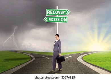 Young businesswoman standing on the road with signpost directing to recession or recovery financial