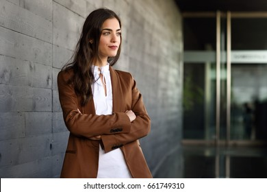 Young businesswoman standing outside of office building. Beautiful woman wearing formal wear. Young girl with brown jacket and trousers.