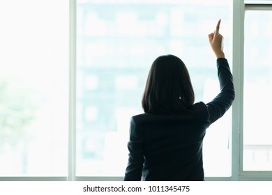 Young businesswoman standing pointing upwards with happy in office