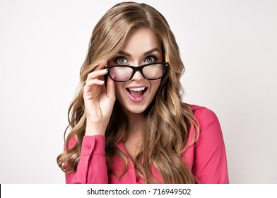 Young businesswoman or student   in  glasses . Beautiful girl in glasses happy and surprised shouts looking forward and holding the glasses . Presenting your product. Expressive facial expressions