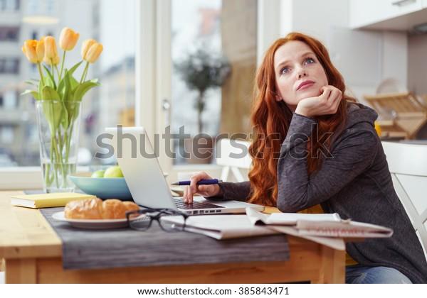 家庭で働く若いビジネスマンや学生が、ノートパソコンと書類を持って、考え深げに空中を見つめながら食卓に座っている