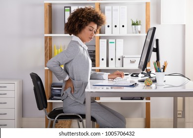 Young Businesswoman Suffering From Back Pain While Working In Office