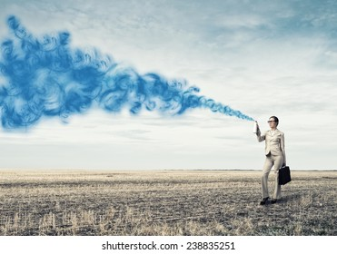 Young businesswoman with suitcase using spray balloon