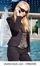 Young businesswoman in sunglasses talking on a phone