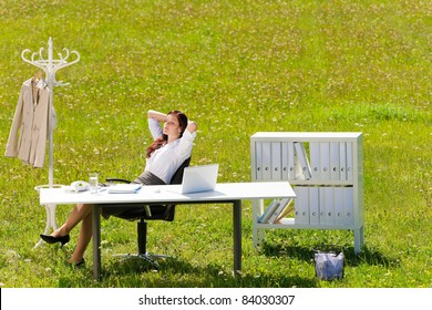 Young businesswoman in sunny meadow nature office relaxing behind table