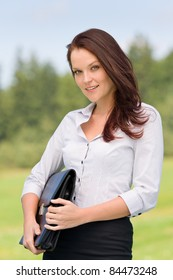 Young businesswoman in sunny nature behind table smiling carry briefcase