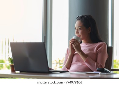 Young businesswoman take break between hours and drink coffee very happy.