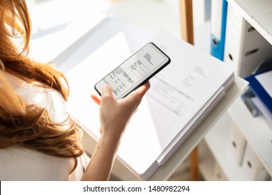 Young Businesswoman Taking Photograph Of Invoice Document Secretly In Office