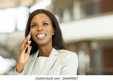 young businesswoman talking on cell phone in modern office