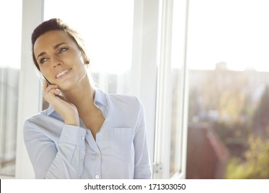 Young businesswoman talking on mobile phone while standing by window in office. Beautiful young female model in bright office.