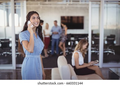 Young businesswoman talking on mobile phone with colleagues in background at creative office
