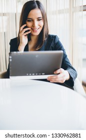 Young businesswoman talking on the phone and using tablet computer in office
