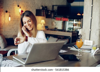 Young businesswoman talking on the phone and checking the time beside laptop on table in cafe