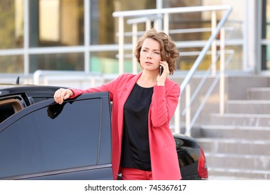 Young businesswoman talking on phone near car