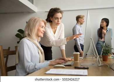 Young businesswoman teaching smiling senior colleague using computer explaining applications work, corporate teacher talking to happy older woman, aged employee or coworker helping with online task